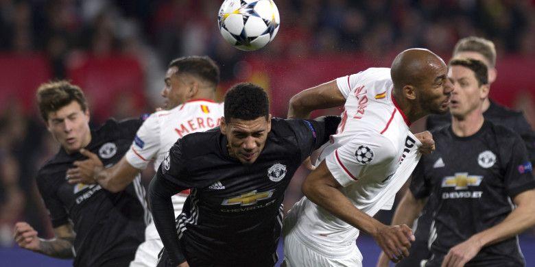 Aksi bek Manchester United, Chris Smalling (tengah), saat berduel dengan gelandang Sevilla, Steven NZonzi (kedua dari kanan), dalam laga leg 1 babak 16 besar Liga Champions 2017-2018 di Stadion Ramon Sanchez Pizjuan, Sevilla, Spanyol, pada Rabu (21/2/2018).
