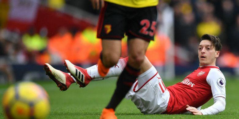 Gelandang Arsenal, Mesut Oezil, terjatuh saat melawan Watford pada pertandingan Liga Inggris di Stadion Emirates, London, Minggu (11/3/2018).