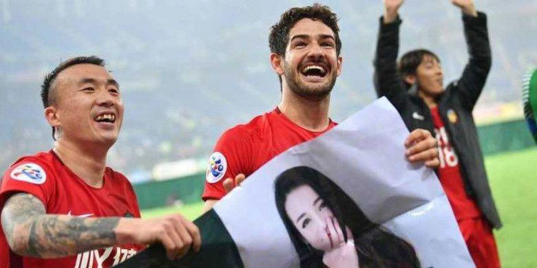 Pemain Tianjin Quanjian, Alexandre Pato (kanan) bersama rekan setimnya memegang poster yang berisi foto dirinya bersama artis China, Dilraba Dilmurat, yang diberikan fans, setelah menang 4-1 atas Jeonbuk Motors di Liga Champions Asia, Rabu (14/3/2018)