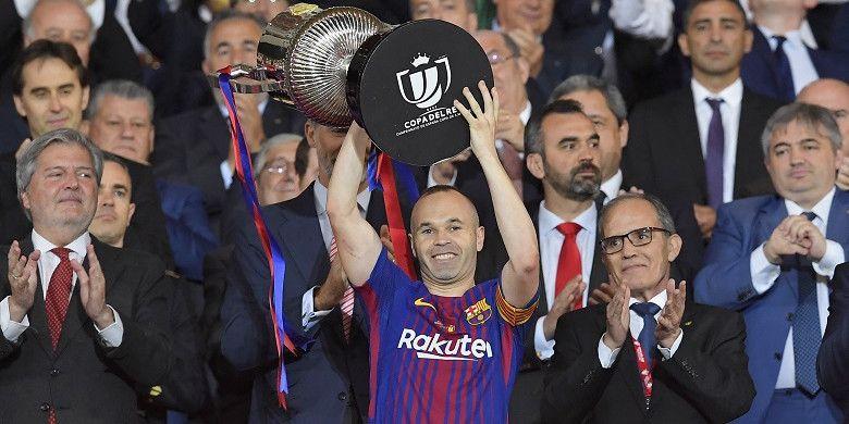 Kapten Barcelona, Andres Iniesta, mengangkat trofi juara Copa del Rey 2018 yang diraihnya pasca mengalahkan Sevilla 5-0 di Stadion Wanda Metropolitano, Madrid, pada Minggu (22/4/2018).