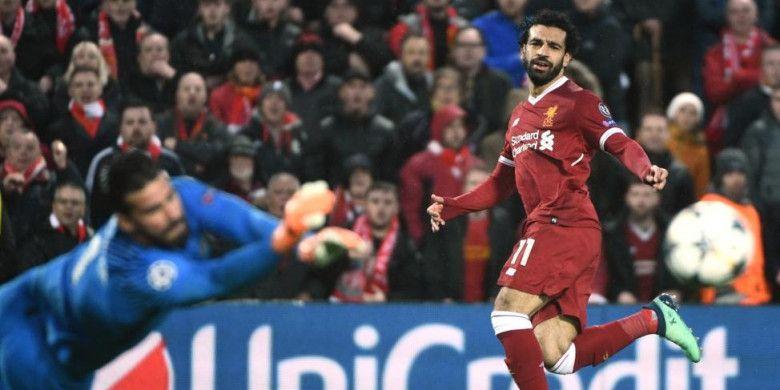 Striker Liverpool, Mohamed Salah (kanan), melepaskan tembakan yang coba dihalau kiper AS Roma, Alisson Becker, dalam partai Liga Champions di Stadion Anfield, Liverpool, 24 April 2018.