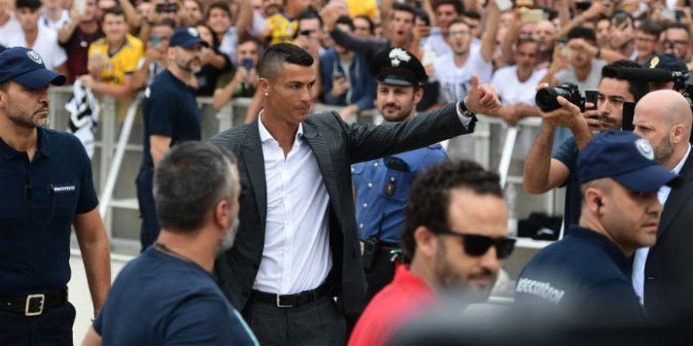 Pemain baru Juventus, Cristiano Ronaldo, melambaikan tangan kepada para suporter saat tiba untuk melakukan tes medis di markas klub di Stadion Allianz, Turin, Senin (16/7/2018).