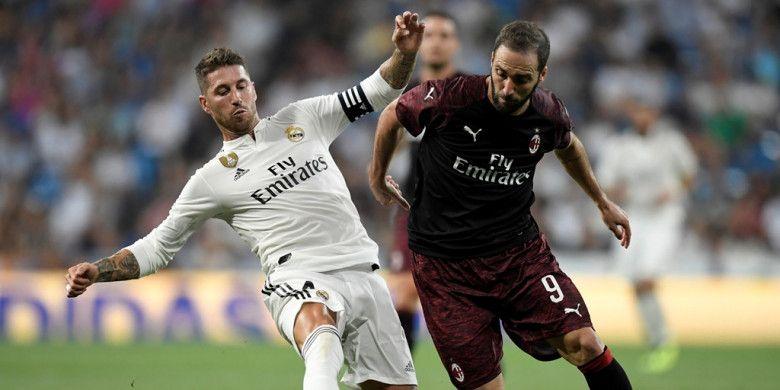 Penyerang AC Milan, Gonzalo Higuain (kanan), berduel dengan bek Real Madrid, Sergio Ramos, dalam laga Trofeo Santiago Bernabeu di Stadion Santiago Bernabeu, Madrid, Spanyol pada 11 Agustus 2018.