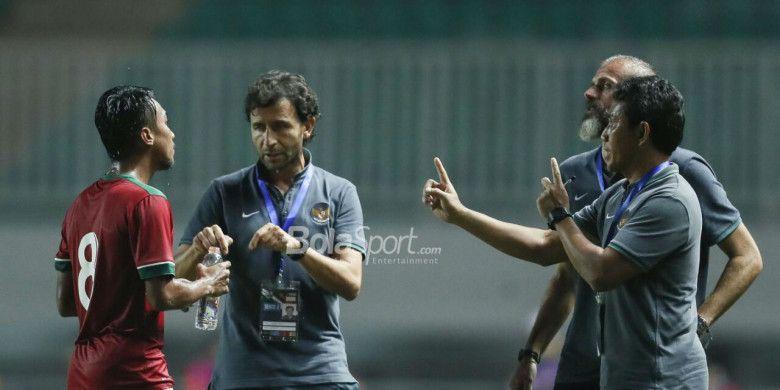 Pelatih Timnas U-23 Indonesia, Luis Milla (tengah), beserta asisten pelatih Bima Sakti (kanan) memberikan instruksi kepada Muhammad Hargianto pada laga PSSI Anniversary Cup 2018 kontra Bahrain di Stadion Pakansari, Bogor, Jumat (27/4/2018)