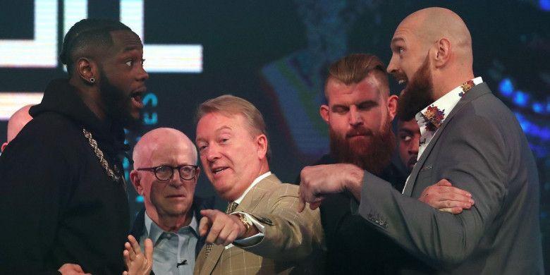Juara dunia kelas berat versi WBC asal Amerika Serikat, Deontay Wilder (kiri), dan mantan juara dunia kelas berat dari Inggris, Tyson Fury, dipisahkan promotor Frank Warren pada sesi jumpa pers di London, Inggris, Senin (1/10/2018).