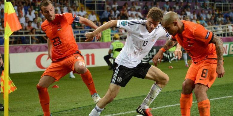Penyerang timnas Jerman, Thomas Mueller (tengah), dijaga ketat dua pemain Belanda, Rafael van der Vaart (kiri) dan Nigel de Jong dalam partai Piala Eropa 2012 di Metalist Stadium, Kharkiv, 13 Juni 2012.