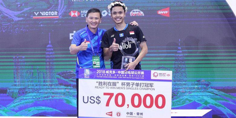 Pebulu tangkis tunggal putra Indonesia, Anthony Sinisuka Ginting, berpose di atas podium juara bersama sang pelatih, Hendry Saputra, setelah mengalahkan Kento Momota (Jepang) pada laga final turnamen China Open 2018 di Changzhou, Minggu (23/9/2018).