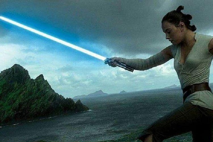 Rey tampak mengayunkan lightsaber milik Anakin Skywalker yang diwariskan kepada Luke Skywalker.