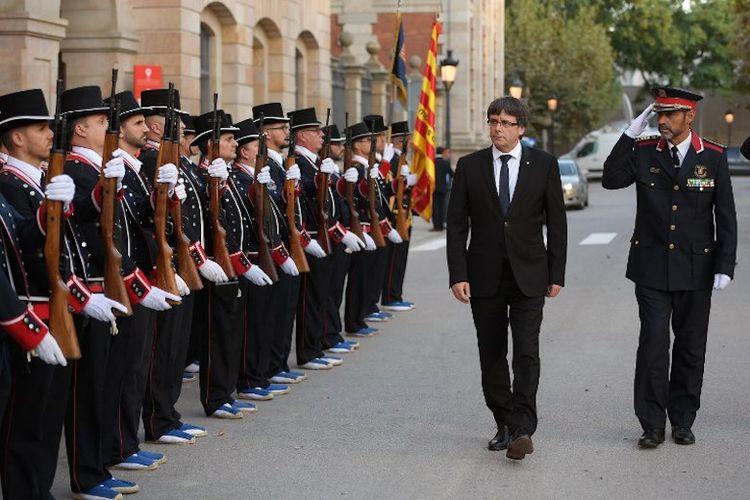 Dokumen foto ini diambil pada 10 September 2017. Presiden Catalonia Carles Puigdemont (dua dari kanan) dan Josep Lluis Trapero (kanan), Kepala Kepolisian Catalonia, menggelar inspeksi terhadap pasukan Mossos DEsquadra sebelum menghadiri seremoni penghargaan terhadap kepolisian Catalonia yang biasa disebut Mossos dEsquadra.