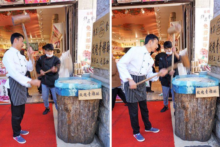 Dua pemuda memukul adonan kacang dan gula di atas gelondongan kayu di sebuah toko penganan di Yunnan Ethnic Village.