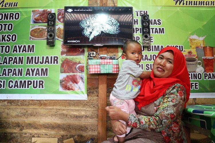 Risma bersama anaknya saat ditemui di warungnya di Distrik Anggi, Kabupaten Pegunungan Arfak, Papua Barat. Risma adalah salah satu pendatang di Kabupaten Pegunungan Arfak yang berasal dari Sulawesi Selatan.