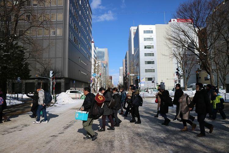 Turis menyeberang jalan untuk menikmati acara Sapporo Snow Festival ke-70 di Odori Park, Kota Sapporo, Prefektur Hokkaido, Jepang, Senin (11/2/2019). Sapporo Snow Festival merupakan acara musim dingin tahunan yang digelar di Kota Sapporo.