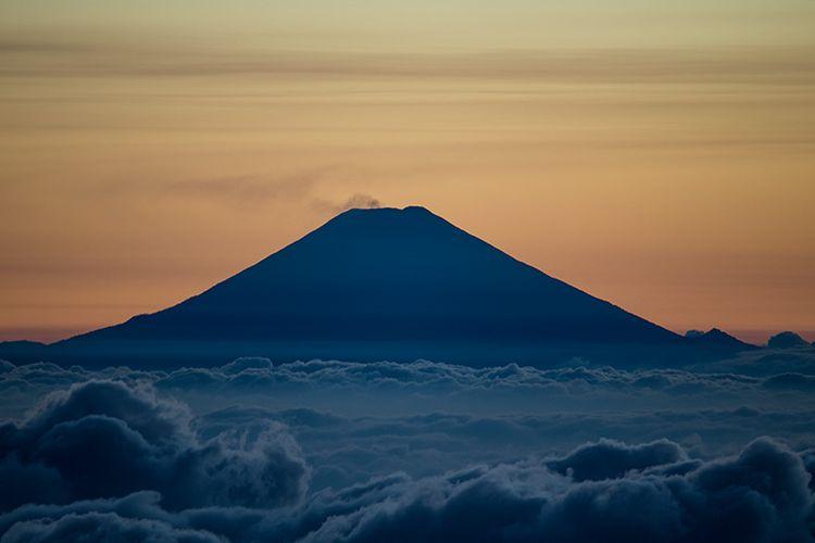 Gunung Slamet dengan puncaknya yang mengeluarkan asap dilihat dari Gunung Sindoro dengan lenza zoom.