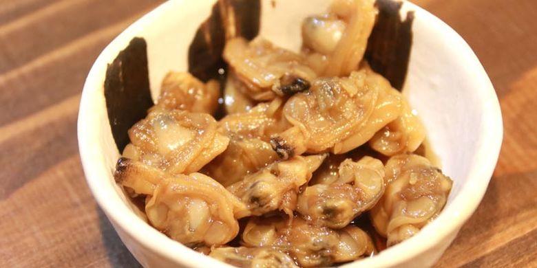 Tsukudani (camilan yang terbuat dari hasil laut yang direbus dan dibumbui dengan shoyu dan gula) dari kerang asari yang dihidangkan bersama ramen di kedai ramen Kuso Oyaji no Tamerai, Prefektur Nagasaki, Jepang ini sangat cocok disantap bersama sake.