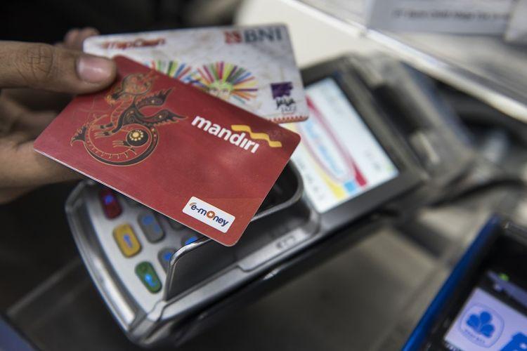 Pekerja menunjukan kartu uang elektronik sebelum isi ulang (top-up) di Bandung, Jawa Barat, Selasa (19/9). Ketua Himpunan Bank-bank Milik Negara (Himbara) Maryono menyatakan sepakat membatalkan rencana pengenaan biaya isi ulang (top-up) uang elektronik menyusul besarnya penolakan dari masyarakat. ANTARA FOTO/M Agung Rajasa/aww/17.
