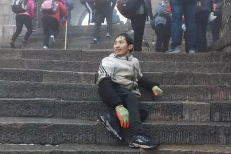 Wang Cunwei asal China mendaki Gunung Tai meski kakinya lumpu karena polio. (Js.ifeng.com)
