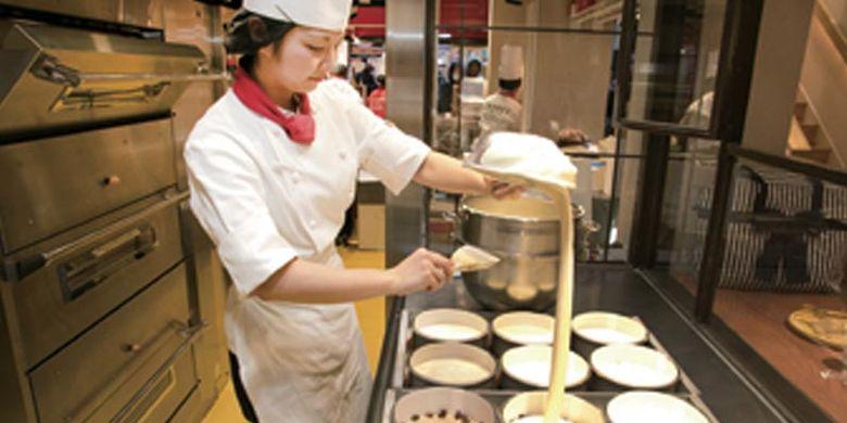 Proses pembuatan cheesecake di Osaka, Jepang. Setelah selesai diaduk, adonan dimasukkan ke dalam masing-masing loyang kertas dari jarak yang cukup tinggi.