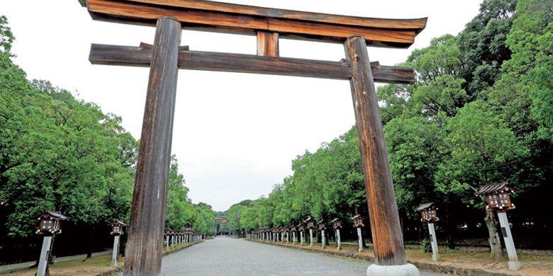 Gerbang kuil (tori) besar akan menyambut kita di jalan masuk Kuil Kashihara Jingu di kota Nara, Jepang. Pohon ek berjajar di kanan dan kiri jalan.