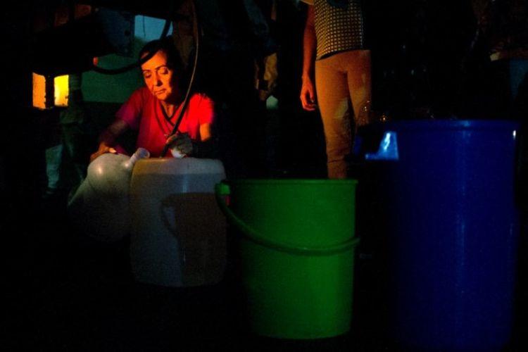 Orang-orang mengantre untuk air minum yang didistribusikan di Chacao, Caracas, Venezuela, Senin (11/3/2019). (AFP/CRISTIAN HERNANDEZ)