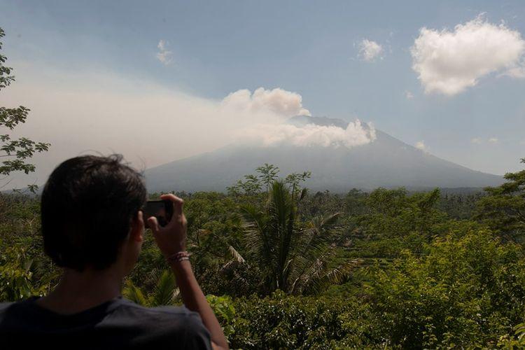 Warga memotret asap yang mulai mengepul dari kawah Gunung Agung dari Pos Pemantauan Desa Rendang, Karangasem, Bali, Selasa (19/9). Petugas pos pemantauan Gunung Agung telah mencatat tingkat kegempaan meningkat drastis dari 180 kali menjadi 366 kali dalam 24 jam terakhir.