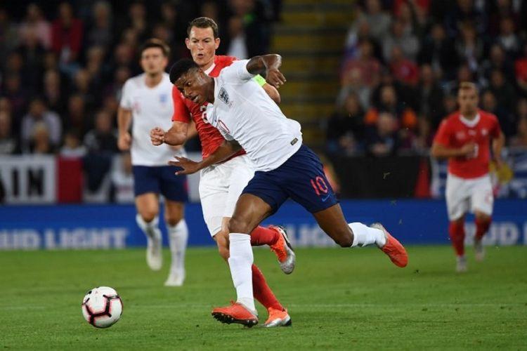 Marcus Rashford mencoba melewati penjagaan Stephan Lichsteiner saat Inggris berhadapan dengan Swiss di Leicester, 11 September 2018.