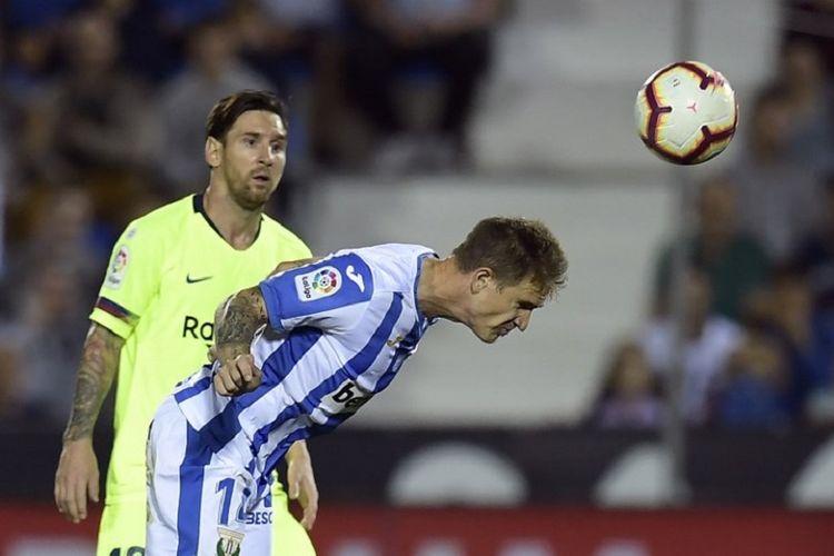Raul Garcia lebih cepat daripada Lionel Messi dalam mengantisipasi datangnya bola pada pertandingan Leganes vs Barcelona di Estadion Municipal de Butarque, 26 September 2018.