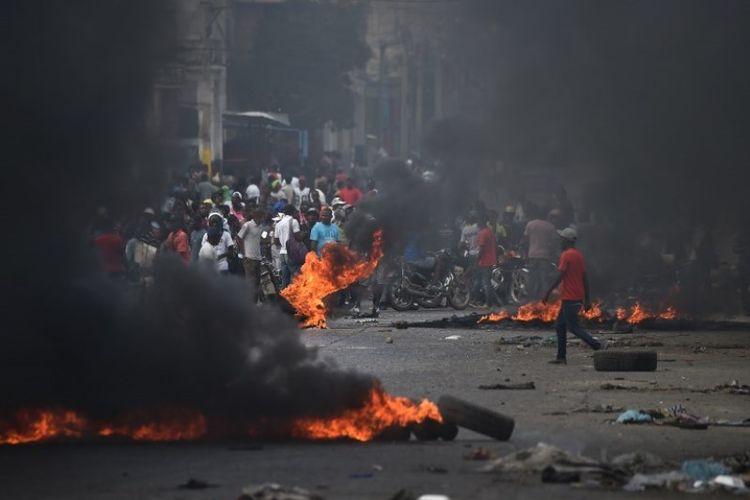 Ban dibakar oleh para demonstran pada hari keempat protes di Port-au-Prince, Haiti, Minggu (10/2/2019), yang mendesak Presiden Haiti Jovenel Moise mundur. (AFP/RETAMAL HECTOR)