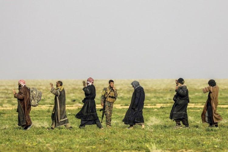 Seorang tentara Pasukan Demokratik Suriah (SDF) yang didukung AS berdiri mengawasi orang-orang yang mengantre di area pemeriksaan setelah dievakuasi dari desa Baghouz,  provinsi Deir Ezzor di Suriah, yang dikuasai ISIS, Selasa (26/2/2019). (AFP/DELIL SOULEIMAN)
