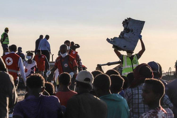 Seorang pria membawa puing di lokasi jatuhnya penerbangan Ethiopian Airlines di Bishoftu, sebuah kota sekitar 60 kilometer tenggara Addis Ababa, Etiopia, Minggu (10/3/2019). (AFP/MICHAEL TEWELDE)