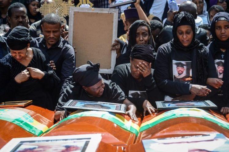 Keluarga korban kecelakaan pesawat Ethiopian Airlines menangisi peti mati kosong selama pemakaman massal di Katedral Holy Trinity di Addis Ababa, Etiopia, Minggu (17/3/2019). (AFP/SAMUEL HABTAB)