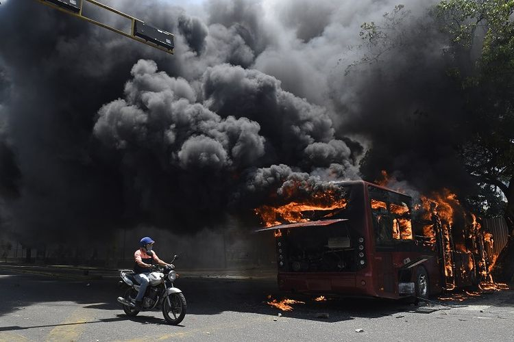 Bus pemerintah dibakar selama bentrokan dengan tentara yang setia kepada Presiden Venezuela Nicolas Maduro. Peristiwa ini terjadi di sekitar pangkalan militer La Carlota di Caracas pada Selasa (30/4/2019). (AFP/Federico Parra)