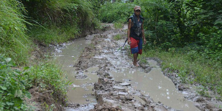 Seorang petani sedang melintasi jalan berlumpur di Wilayah Elar, Kabupaten Manggarai Timur, Flores, Nusa Tenggara Timur, Minggu (28/1/2018).