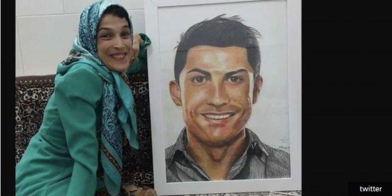 Seniman asal Iran, Fatemeh Hamami, berpose dengan lukisan Cristiano Ronaldo hasil karyanya.