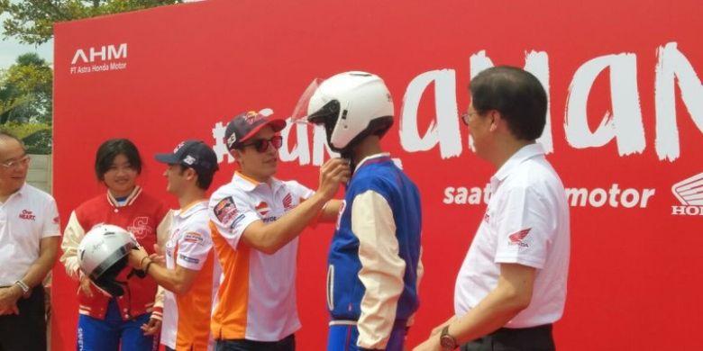 Pebalap Repsol Honda Team, Marc Marquez, memasangkan helm kepada anak SMA TSM Honda, di Astra Biz Center, BSD, Tangerang, Selasa (17/10/2017).