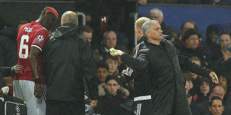 Manajer Manchester United, Jose Mourinho (kanan), melempar ban kapten yang sebelumnya dipakai Paul Pogba (kiri), kepada Ashley Young dalam laga penyisihan Grup A Liga Champions melawan Basel di Stadion Old Trafford, Manchester, Inggris, 12 September 2017. Pogba Ditarik keluar akibat cedera.