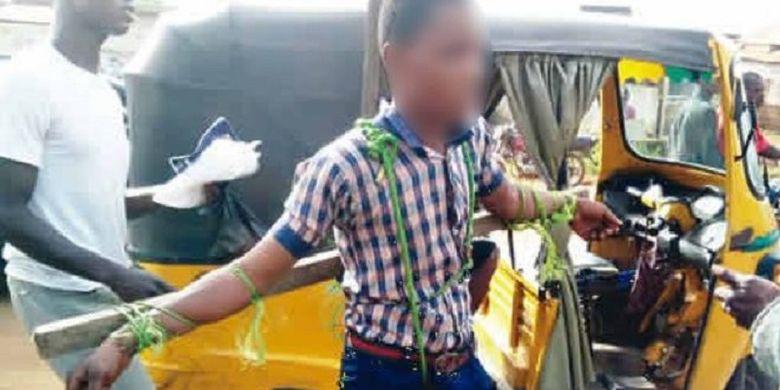 Seorang anak yang diikat di batangan kayu. Dia disiksa bersama seorang murid perempuan lainnya karena terlambat ke sekolah.