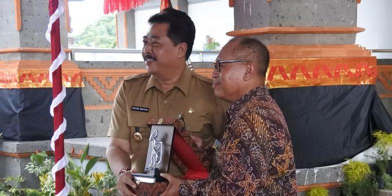 Wakil Bupati Gianyar Anak Agung Gede Mayun (kiri) sedang menerima penghargaan dari Dirut BPJS Ketenagakerjaan.