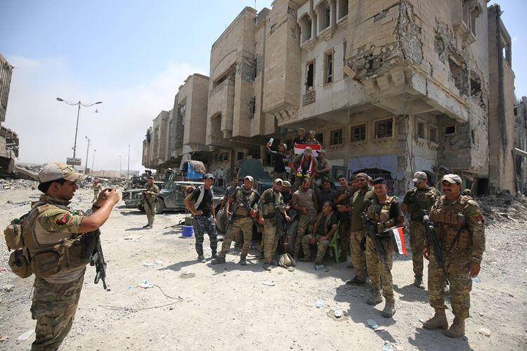 Sekelompok prajurit Irak berfoto bersama di Kota Tua Mosul setelah tugas mereka merebut kota itu dari tangan ISIS dinyatakan telah berakhir dengan kemenangan.