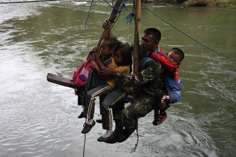 Beberapa pelajar siswa berada di tali penyeberangan darurat di Sungai Ranteangin dibantu personil Kodim 1412 Kolaka saat hendak ke sekolah dari Desa Maroko ke Desa Tinokari, Wawo, Kolaka Utara, Sulawesi Tenggara, Jumat (28/7). Pelajar di Kecamatan Wawo hanya mengandalkan tali penyeberangan darurat untuk pergi ke sekolah mereka.