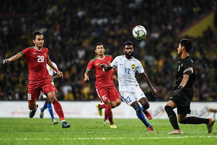 Penyerang Malaysia, Thanabalan A/L Nadarajah (tengah), berusaha menggapai bola yang mengarah ke penjaga gawang Timnas U-22 Indonesia, Satria Tama Hardiyanto (kanan), dalam pertandingan semifinal SEAE Games 2017 di Shah Alam Stadium, Shah Alam, Sabtu (26/8/2017).