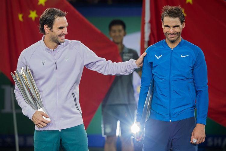 Petenis Swiss, Roger Federer (kiri), yang menjadi juara Shanghai Masters, bercanda dengan petenis Spanyol, Rafael Nadal, usai menerima trofi di Shanghai, 15 Oktober 2017.