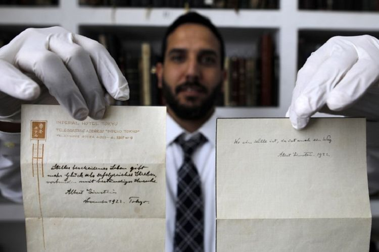 A picture taken on October 19, 2017, shows Gal Wiener, owner and manager of the Winners auction house in Jerusalem, displays two notes written by Albert Einstein, in 1922, on hotel stationary from the Imperial Hotel in Tokyo Japan.  A note that Albert Einstein gave to a courier in Tokyo, briefly describing his theory on happy living, has surfaced after 95 years and is up for auction in Jerusalem. / AFP PHOTO / MENAHEM KAHANA