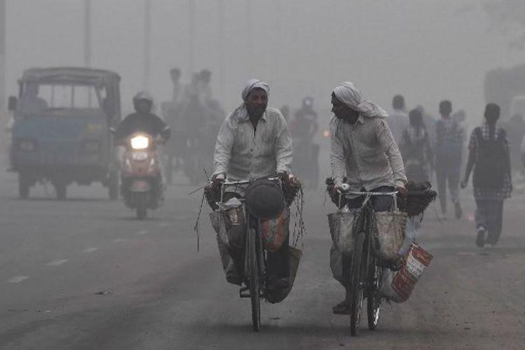 Suasana jalan di New Delhi yang diselimuti kabut tebal akibat polusi terparah, Selasa (7/11/2017). (AFP/Prakash Singh)