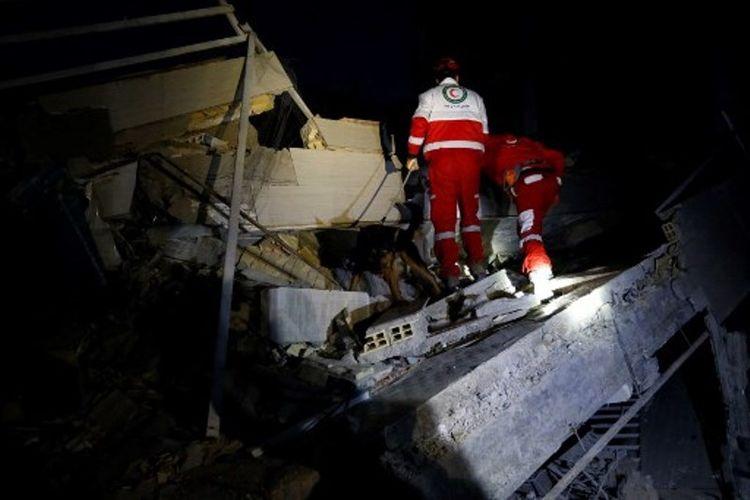 Petugas penyelamat sedang melakukan pencarian korban gempa Iran-Irak di kota Sarpol-e Zahab, Iran, pada Senin (13/11/2017). (AFP/Pouria Pakizeh/Isna)