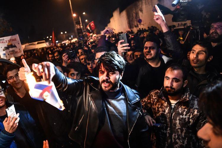 Seorang demonstran membakar bendera Israel yang dicetak dalam sebuah kertas dalam aksi demonstrasi mengecam Amerika Serikat dan ISrael, di depan gedung konsulat AS, di Istanbul pada Rabu (6/12/2017). (AFP/Ozan Kose)