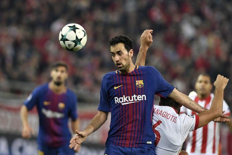 Gelandang FC Barcelona, Sergio Busquets, berduel dengan gelandang Olympiakos, Panagiotis Tachtsidis, pada laga Grup D Liga Champions, di Stadion Karaiskakis, Piraeus, 31 Oktober 2017.
