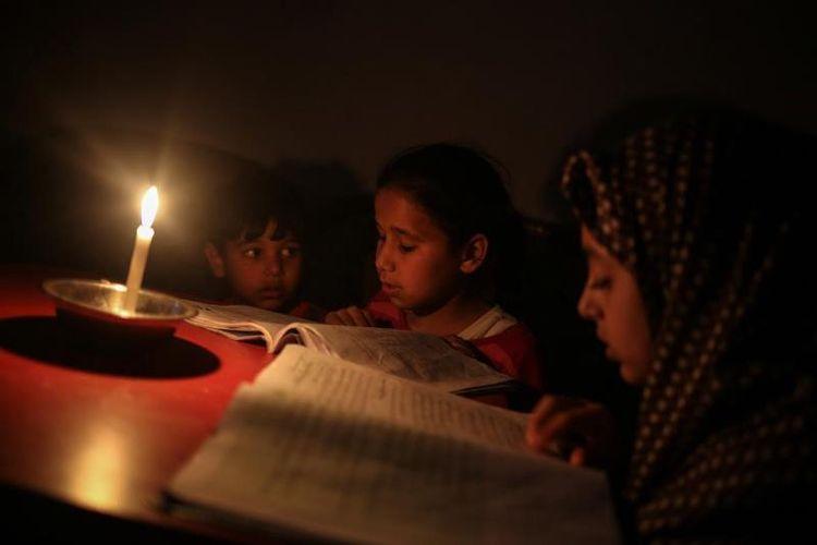 Anak-anak Palestina membaca buku dengan penerangan lilin karena pemadaman listrik di Kamp Jabalia di Gaza, pada tanggal 27 Juni 2017. (Anadolu Agency via Middle East Monitor)