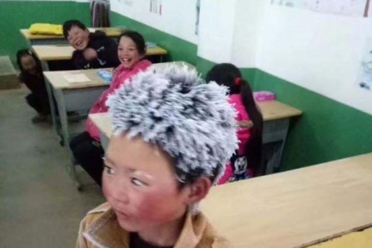 Foto yang memperlihatkan Wang Fuman datang dalam keadaan setengah beku untuk mengikuti ujian akhir sekolah di Shaoton, Provinsi Yunnan, China (10/1/2018).