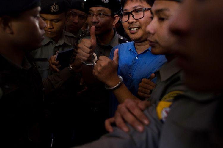 Jurnalis Reuters, Wa Lone (tengah) dijaga polisi ketika tiba di pengadilan di Yangon, Myanmar, Rabu (10/1/2018). (AFP/Ye Aung Thu)