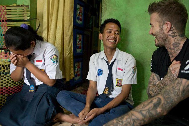 Duta Kehormatan UNICEF David Beckham tertawa bersama Sripun (15) dan temannya, Ego, di rumah nenek Ego di Semarang, Jawa Tengah, Indonesia, 27 Maret 2018. Sripun diunjuk oleh lingkungannya untuk menjadi agen perubahan dan berpartisipasi dalam program anti-bullying yang diinisiasi UNICEF.